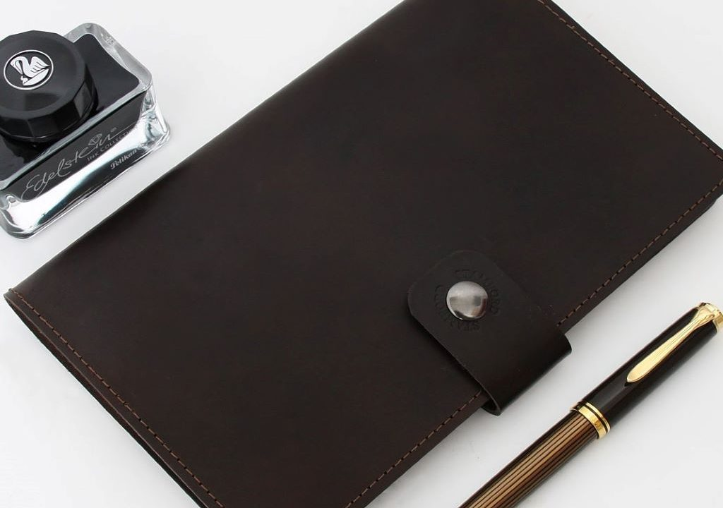 A leather notebook with a pen and a bottle of ink