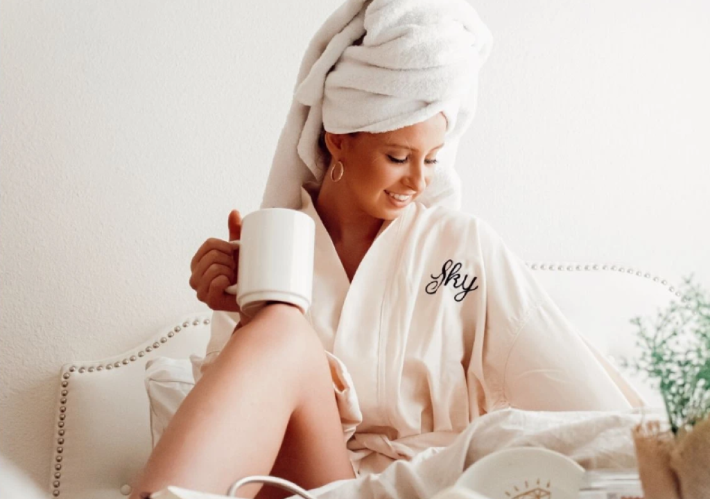 A woman in bed in a bathrobe with a monogramm